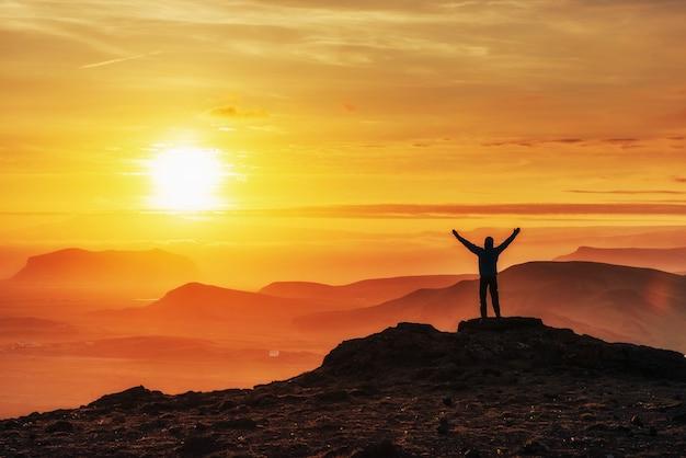 Gelukkig man permanent op een klif bij zonsondergang