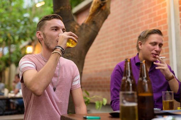 Gelukkig man praten en bier drinken met vrienden