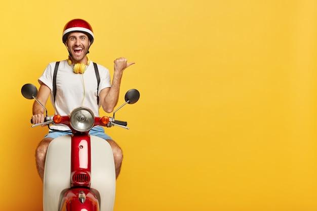 Gelukkig man rijdt op een scooter, wijst richting weg, wijst duim rechts op lege ruimte op gele achtergrond, gekleed in vrijetijdskleding en helm, maakt gebruik van koptelefoon, heeft een vrolijke gezichtsuitdrukking