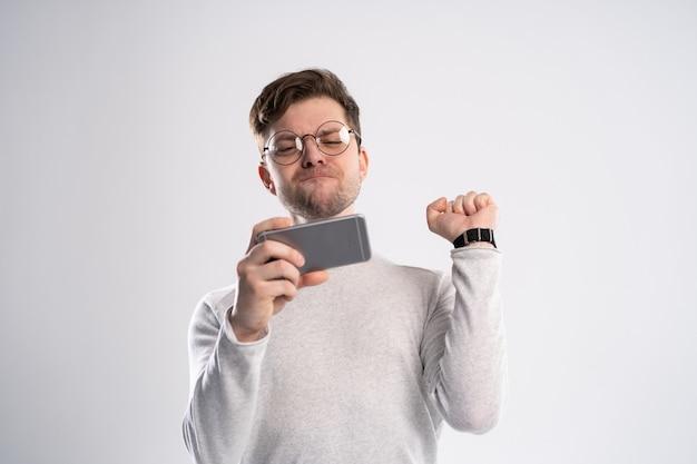 Gelukkig man smartphone houden en viert zijn succes