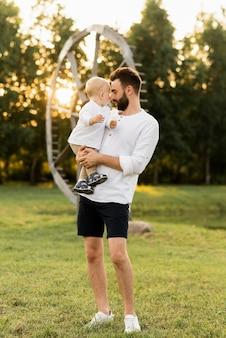 Gelukkig man spelen met zijn zoontje buiten op een zonnige dag