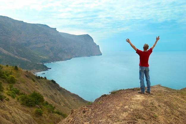 Gelukkig man staande op de klif met handen omhoog kijken naar de zee
