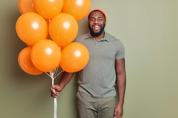 Gelukkig man staat blij gekleed in vrijetijdskleding houdt bos van oranje opgeblazen ballonnen vormt binnen tegen kaki muur