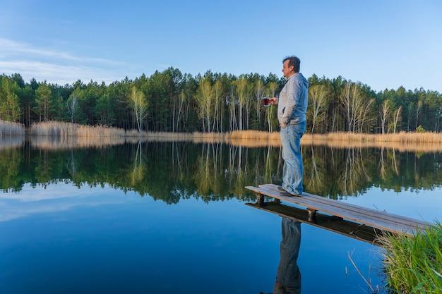 Gelukkig man staat op een houten pier met glazen kopje thee in de buurt van lentebos op een kalm meer in oekraïne. natuur en reizen concept. mooi en kleurrijk tafereel