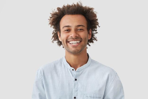 Gelukkig man student met afro kapsel vertoont witte tanden, in goed humeur na de lessen