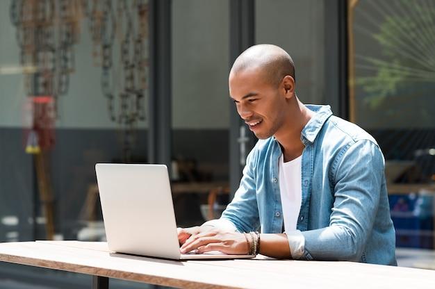 Gelukkig man tekst intoetsen op laptop in een moderne coffeeshop