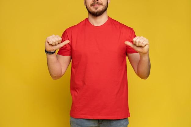 Gelukkig man van bezorgservice in rood t-shirt en pet geïsoleerd over gele muur