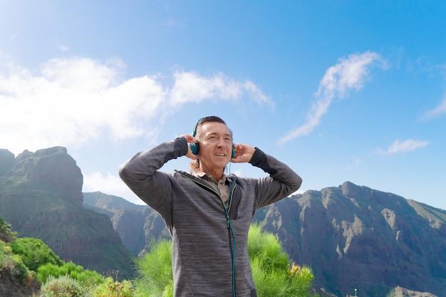 Gelukkig man van middelbare leeftijd reiziger hoofdtelefoon dragen, muziek luisteren en glimlachen