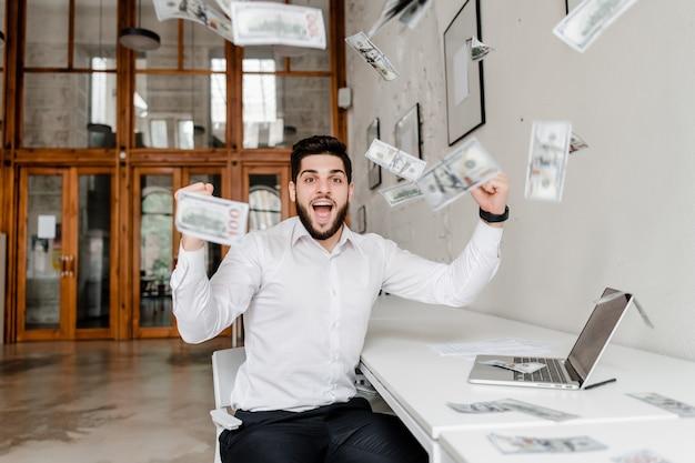 Gelukkig man verdient veel geld op kantoor, dollars vallen uit de lucht