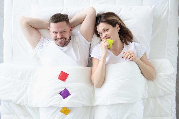 Gelukkig man vrouw liggen op bed met condooms gezond intiem leven concept