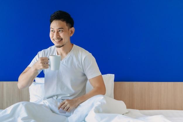 Gelukkig man wakker op zijn bed op blauwe kopie ruimte achtergrond copy