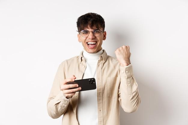 Gelukkig man winnen op smartphone, mobiele telefoon vasthouden en hand opsteken, ja schreeuwen van vreugde, staande op een witte muur.