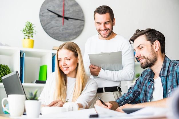 Gelukkig mannelijk en vrouwelijk zakenlui die aan laptop werken