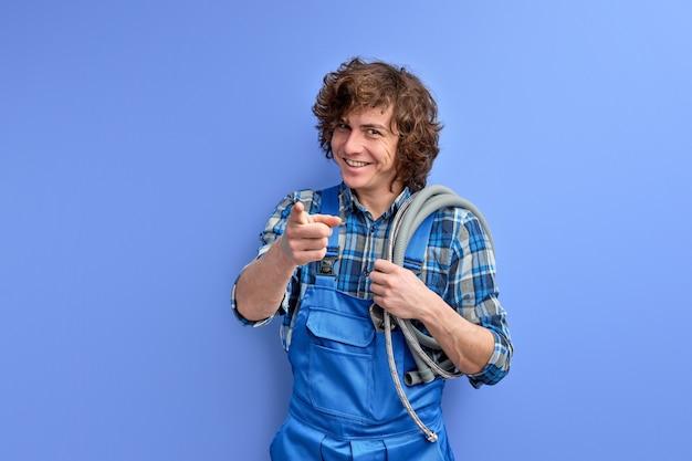 Gelukkig mannelijke architect en loodgieter wijzende vinger op camera en lachend op blauwe achtergrond