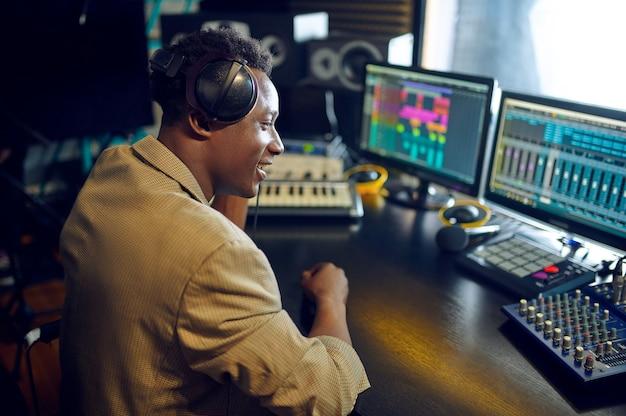 Gelukkig mannelijke dj in koptelefoon bezig met een nieuwe hit, opnamestudio interieur op achtergrond. synthesizer en audiomixer, muzikantenwerkplek, creatief proces