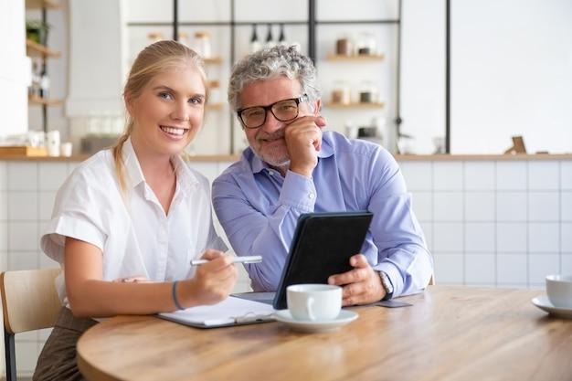 Gelukkig mannelijke en vrouwelijke collega's van verschillende leeftijden zitten aan tafel bij co-working, samen met behulp van tablet, notities schrijven, camera kijken, glimlachen