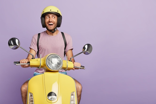 Gelukkig mannelijke fietser of koerier rijdt gele scooter, draagt beschermende helm, casual t-shirt, poseert op zijn eigen transport, kijkt vreugdevol opzij, vervoert iets, geïsoleerd op paarse muur, lege ruimte