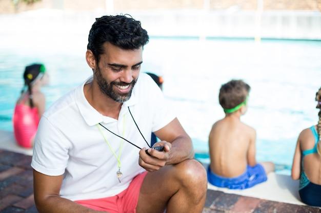 Gelukkig mannelijke instructeur kijken naar stopwatch door kinderen bij het zwembad