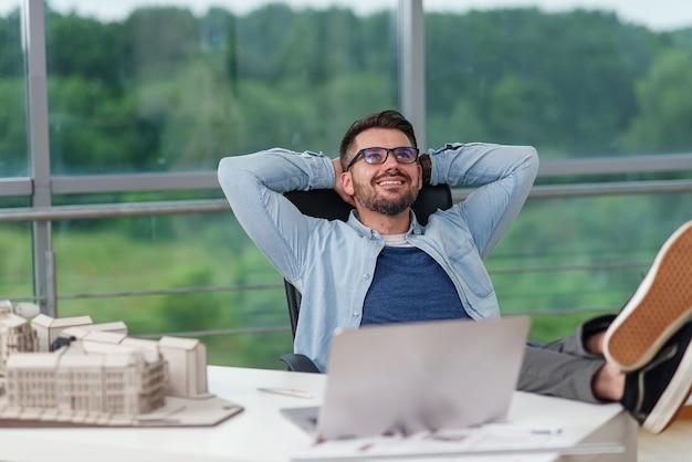 Gelukkig mannelijke kantoormedewerker in vrijetijdskleding legde zijn voeten op de werkruimtetafel terwijl hij droomde over rust of vakanties. j