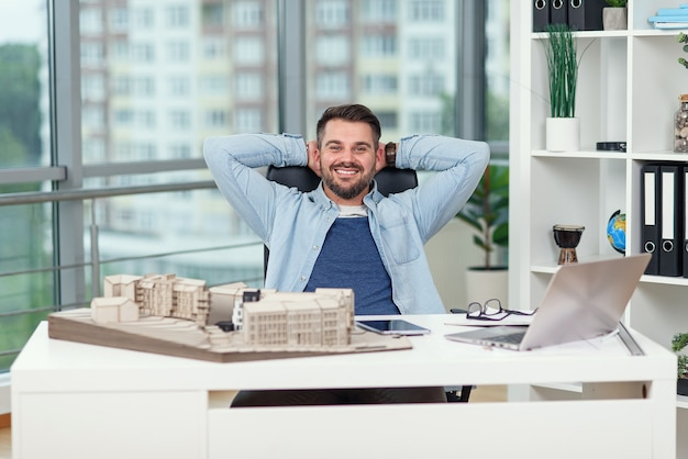 Gelukkig mannelijke kantoormedewerker in vrijetijdskleding legde zijn voeten op de werkruimtetafel terwijl hij droomde over rust of vakanties. vrolijke architect ontspant op de werkplek en voltooit zijn project met succes.