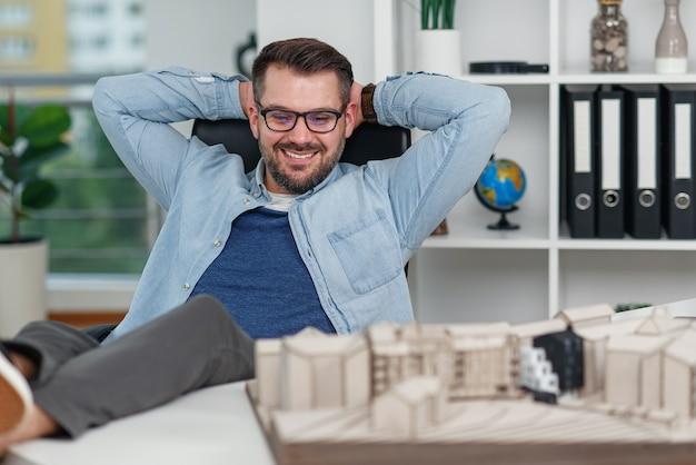 Gelukkig mannelijke kantoormedewerker in vrijetijdskleding legde zijn voeten op de werkruimtetafel terwijl hij droomde over rust of vakanties.