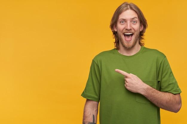 Gelukkig mannelijke, knappe bebaarde man met blond kapsel. groen t-shirt dragen. heeft tatoeages. en wijzende vinger naar links op kopie ruimte, geïsoleerd over gele muur