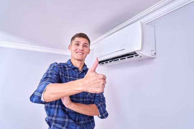Gelukkig mannelijke meester in blauw shirt geïnstalleerd airconditioner binnenshuis en is blij met zijn werk, duim opdagen en glimlachen