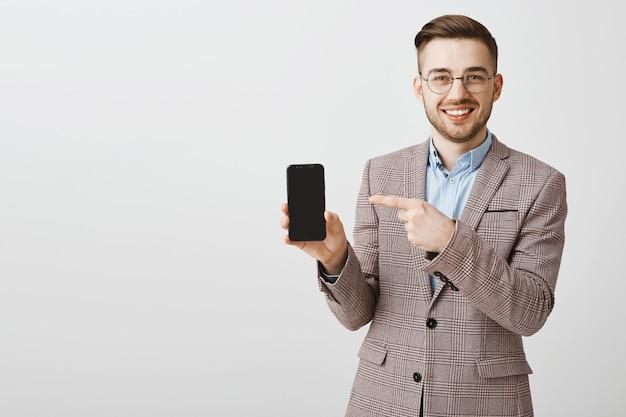 Gelukkig mannelijke ondernemer in pak wijzende vinger op smartphone puin, met mobiele applicatie