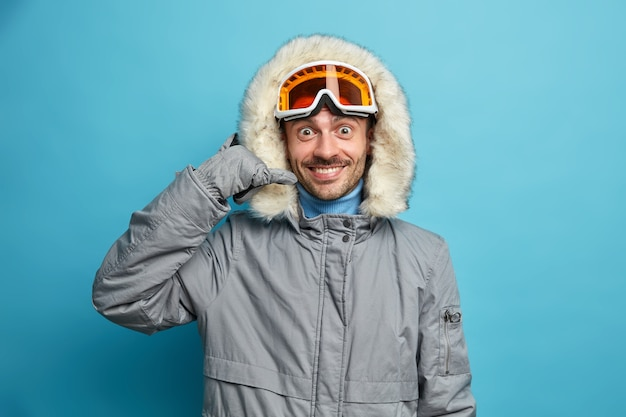 Gelukkig mannelijke snowboarder draagt winterjas met capuchon maakt telefoongebaar positief glimlacht.