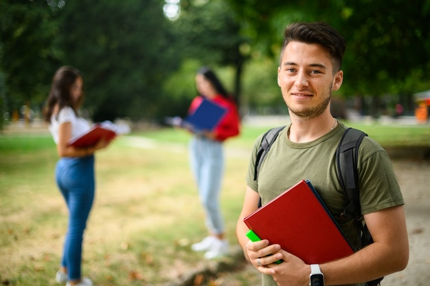 Gelukkig mannelijke student buiten glimlachen