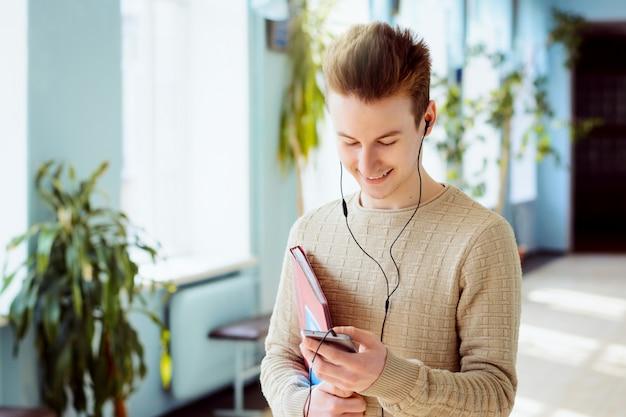 Gelukkig mannelijke student met behulp van de mobiele telefoon en luistert naar muziek