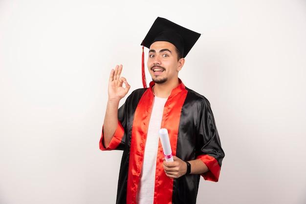 Gelukkig mannelijke student met diploma ok teken op wit maken.