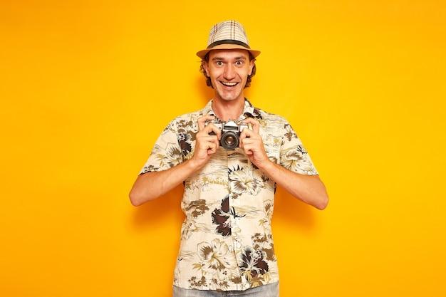 Gelukkig mannelijke toerist houdt camera in handen voor hem geïsoleerd op gele achtergrond ruimte voor tekst