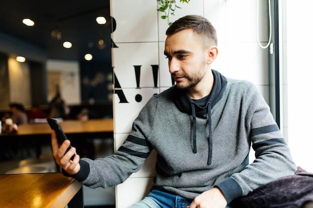 Gelukkig mannetje dat smartphone gebruikt bij moderne coffeeshop