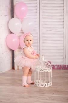 Gelukkig meisje 1 jaar oude ballerina in studio op lichte muur met roze ballen