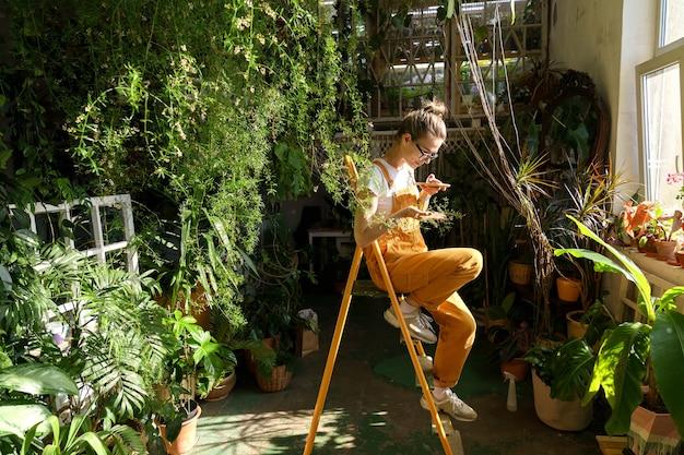 Gelukkig meisje bloemist in overall ontspannen thuis neemt een foto van kamerplant takje op mobiele telefoon