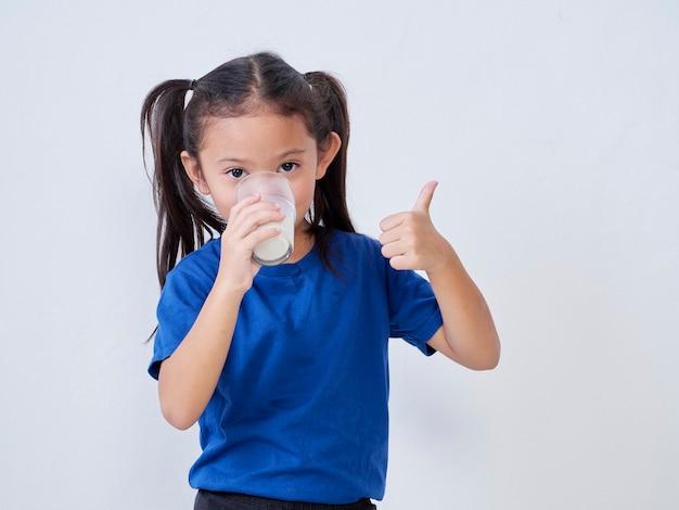 Gelukkig meisje consumptiemelk en duim omhoog teken tegen licht tonen