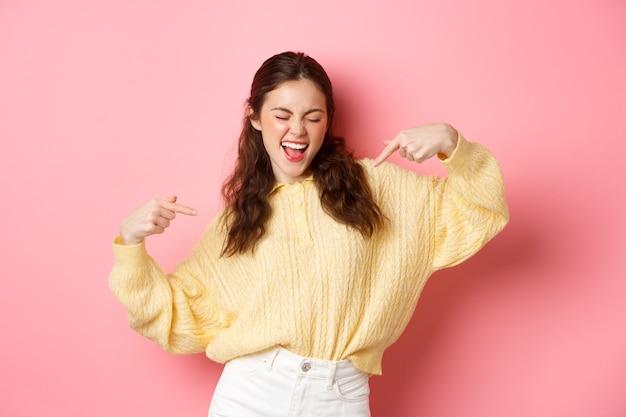 Gelukkig meisje danst en wijst naar zichzelf, ziet er zelfverzekerd uit, wint en verheugt zich, maakt kies mij gebaar, staande over roze muur.