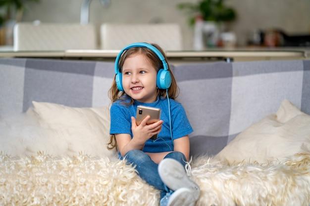 Gelukkig meisje dat aan muziek in blauwe hoofdtelefoons luistert, thuis