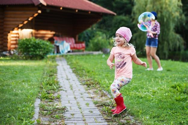 Gelukkig meisje dat buiten met zeepbellen speelt een klein meisje laat een zeepbel knappen