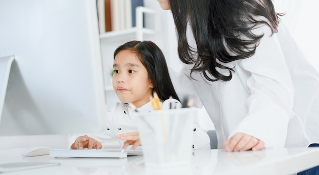 Gelukkig meisje dat computer met haar moeder bekijkt