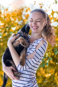 Gelukkig meisje dat een duitse herderpuppy en het glimlachen houdt. een hond kopen en kopen. hondenkus. liefde voor dieren.