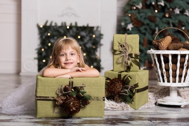 Gelukkig meisje dat een grote doos met een gift over haar hoofd houdt. wintervakantie, kerstmis en mensenconcept.