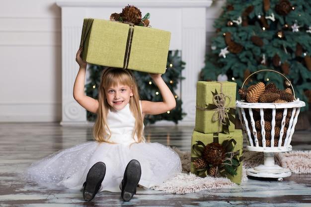 Gelukkig meisje dat een grote doos met een gift over haar hoofd houdt.
