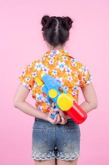 Gelukkig meisje dat een roze achtergrondwaterkanon houdt.