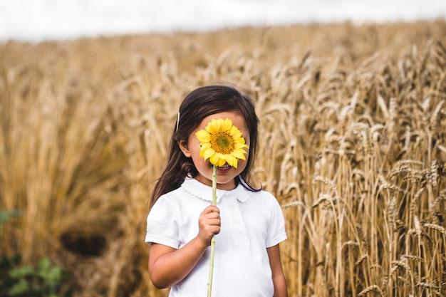 Gelukkig meisje dat een zonnebloem op het gebied ruikt.