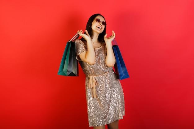 Gelukkig meisje dat elegante kleding en rode zonnebril draagt ?? die het winkelen zakken op rode achtergrond houdt.