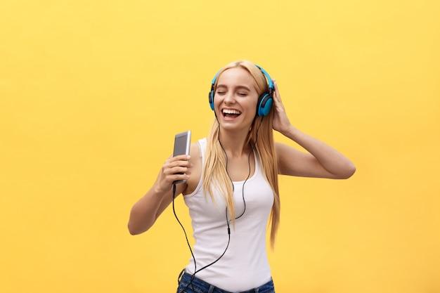Gelukkig meisje dat en aan de muziek danst luistert die op een gele achtergrond wordt geïsoleerd