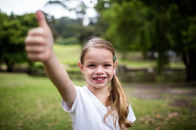 Gelukkig meisje dat haar duimen in het park toont