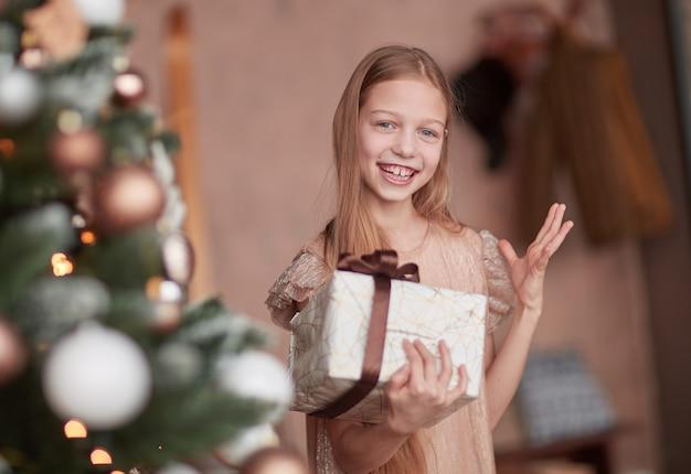 Gelukkig meisje dat haar huidige kerstmis bekijkt.